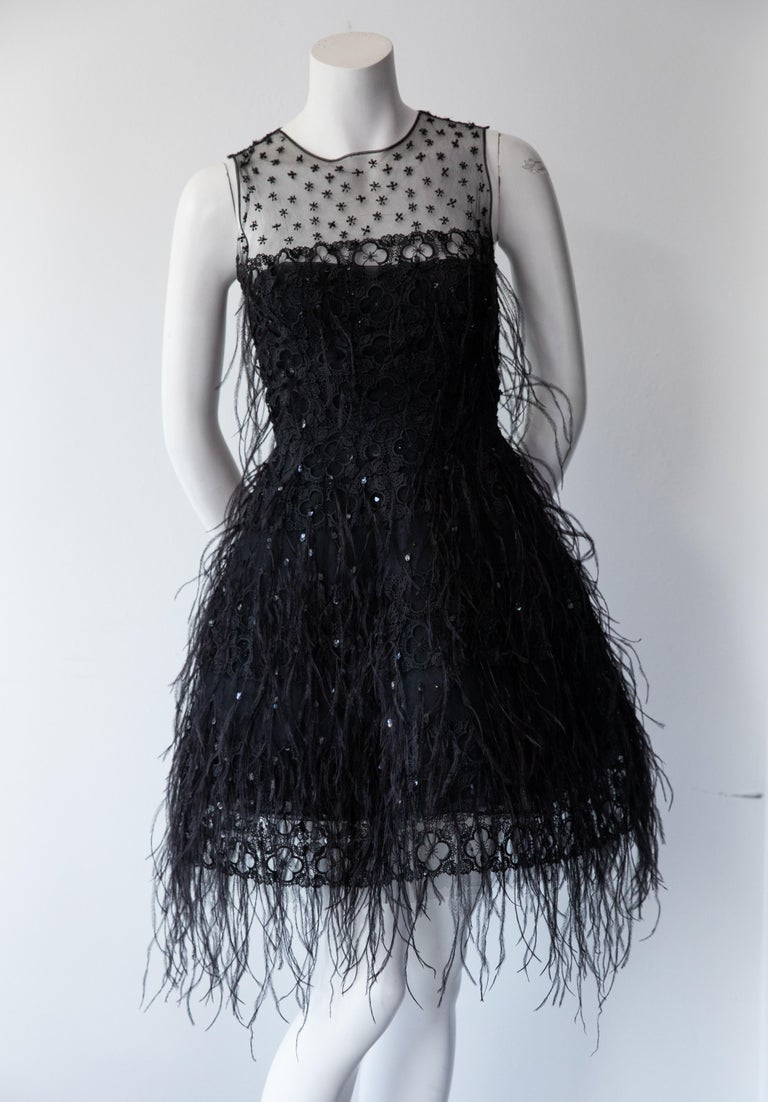 In this structured Oscar De La Renta cocktail dress you will embody the essence of classic, elevated glamour. Black feathers and rhinestones add texture to this sleeveless black dress, while the embroidered sheer mesh yoke adds reveals the slightest