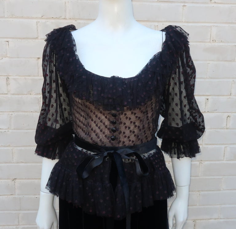 Oscar de La Renta two piece black dress with a dot netted peasant style peplum top and full velvet skirt.  The top buttons down the front with a ruffled collar and full sleeves with elasticized cuffs.  It has a nude illusion modesty lining and