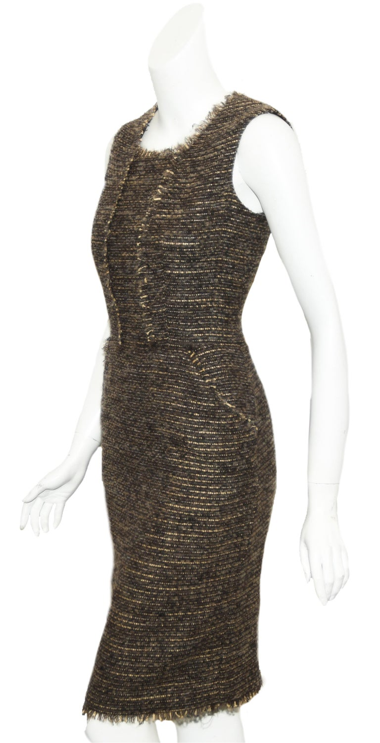 Oscar de la Renta wool tweed/boucle  sleeveless dress in brown and beige tones is from the 2009 fall collection.  This classic dress contains a square neckline that is defined with fringe trim, that continues down the front and accentuates the two