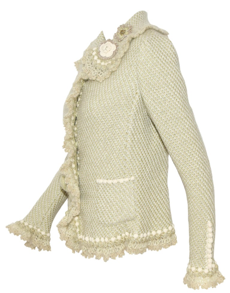 Oscar de la Renta pale green cashmere and wool sweater jacket includes crochet flowers on collar and one pocket.  Sweater jackets features round collar, two front patch pockets and ruffles on the front opening, cuffs and hem.  Excellent Condition!