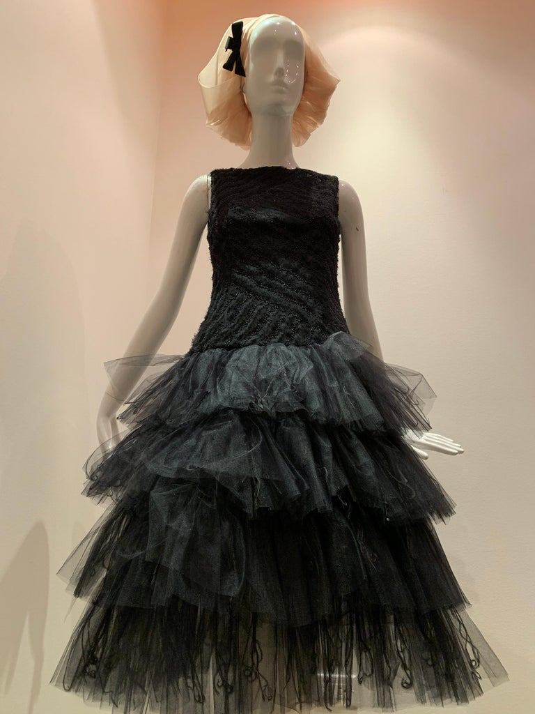 A contemporary Oscar de la Renta ballet-inspired dropped-waist, sleeveless black cocktail dress with multi-tiered tulle skirt embellished with curled ostrich feathers. The ballet neck bodice is embellished with beaded diagonal stripes and gathered