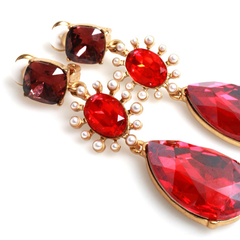 Gold-tone metal Oscar de la Renta ruby colored drop earrings featuring crystals and faux pearl detailing with clip-on closures with rubber comfort pads.