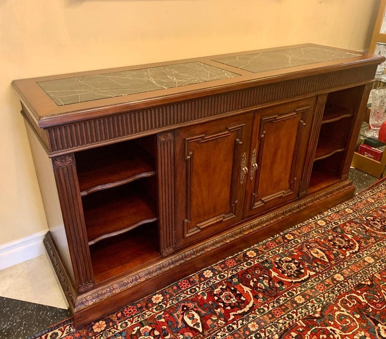 Couture designer Oscar De La Renta for Century Furniture Company handcrafted, distressed mahogany finish, buffet or credenza cabinet featuring an attractive fluted apron and side columns, as well as a carved acanthus leaf motif base. Distressed