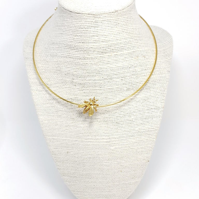 A golden wire choker accented with a bee, by Oscar de la Renta.  Gold-plated.  Hallmarks: Oscar de la Renta, Made in USA