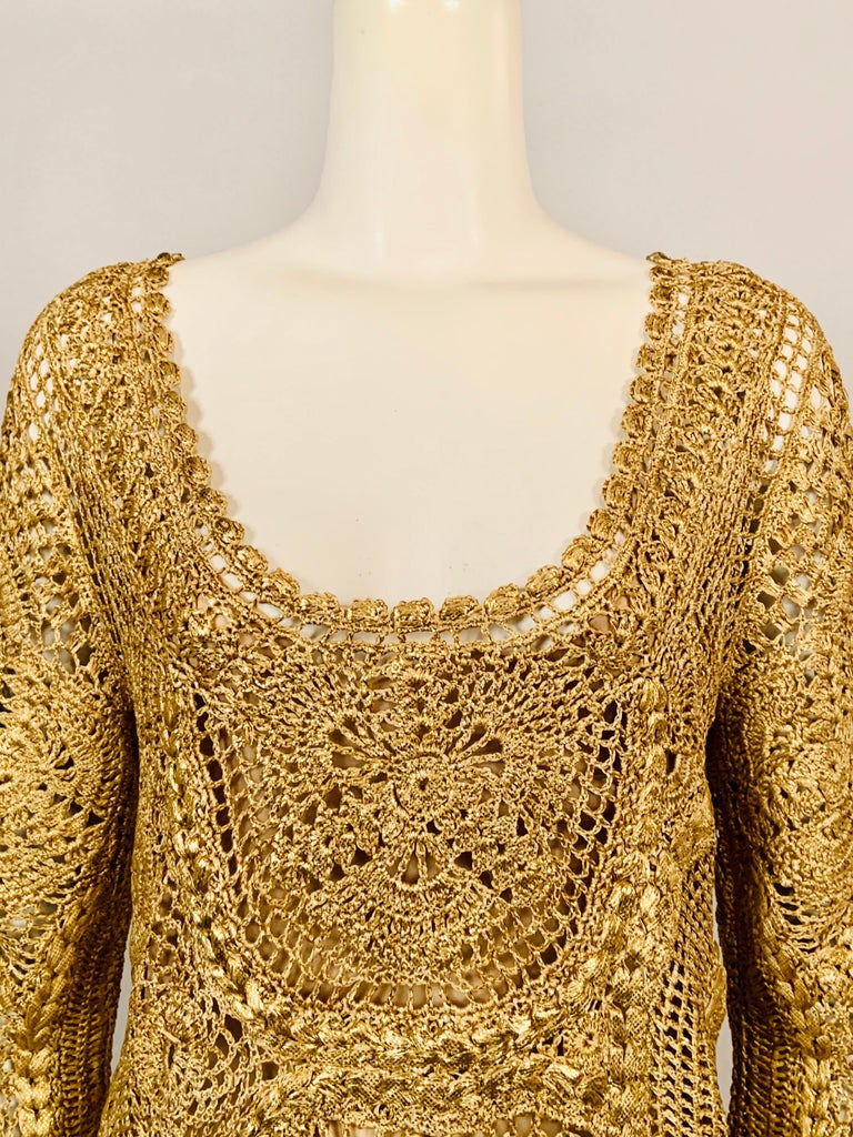 Oscar de la Renta designed a luxurious gold lacquered silk hand crocheted pullover tunic for the Spring 2010 collection. The top has a scoop neckline, three quarter length sleeves, and a scalloped hem.  It comes with a pale gold camisole made from