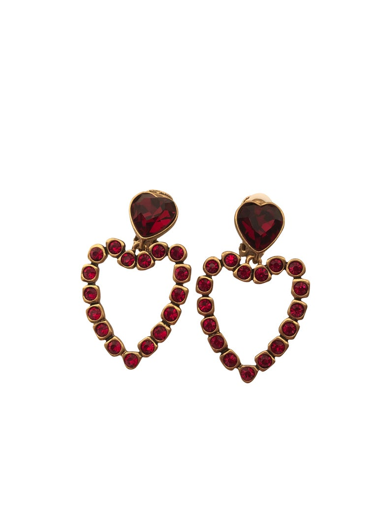 Stunning Oscar de la Renta love heart drop earrings with ruby red diamantes set in gold toned hardware. Clip on closure. Made in USA.