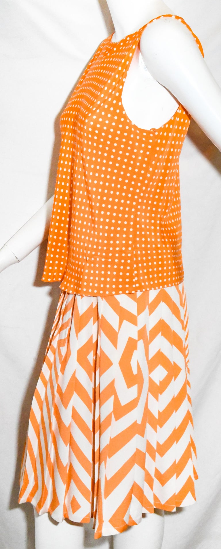 Oscar de la Renta orange and white two piece dress that incorporates a polka dot sleeveless top and an abstract  geometric pleated skirt.  The top contains 5 snaps, at back, for closure.  The pleated skirt includes a hook and eye and zipper, for