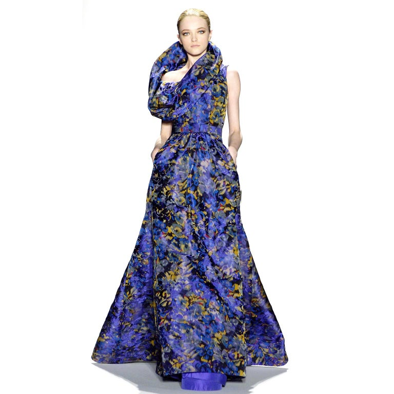 This purple floral Oscar de la Renta dress is incredibly unique and has a very flattering silhouette. We are showing it in a long version presented during the Fall Winter Oscar de la Renta runway show.The dress has a very structured and has a
