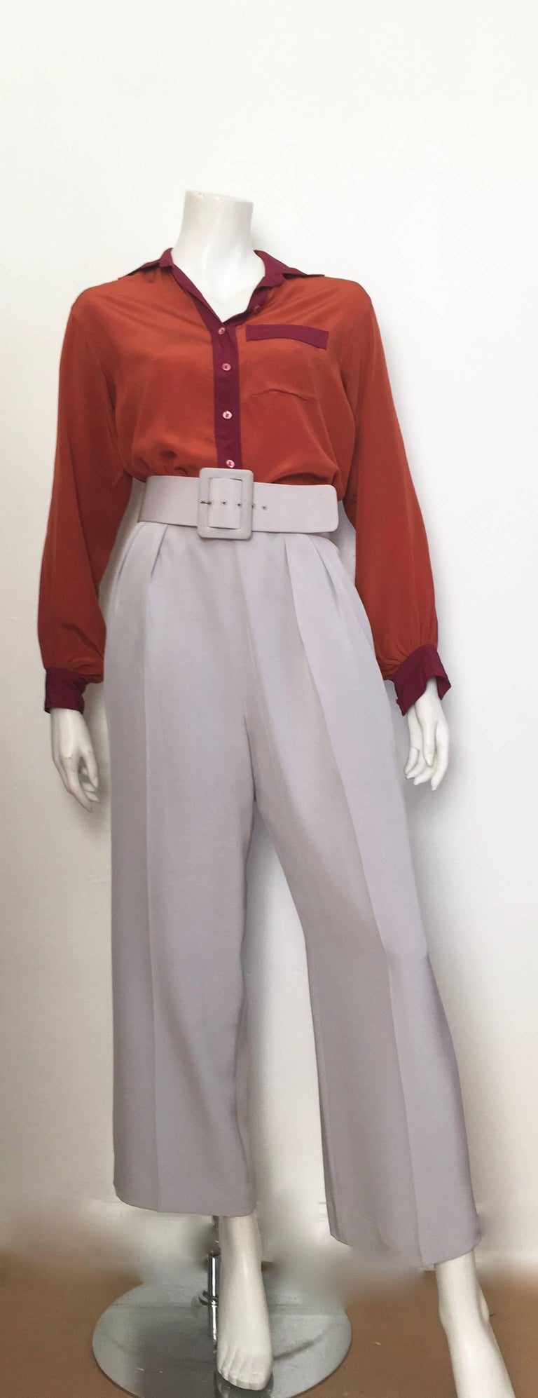Oscar de la Renta silk silver grey pleated pants with pockets & belt is labeled a size 8 but fits a size 6.  The waist is 29