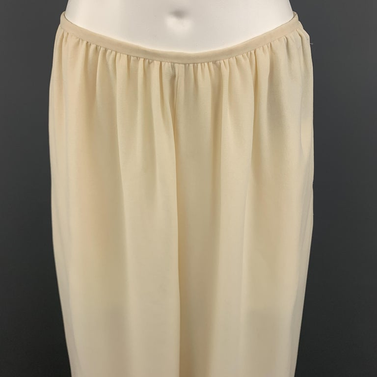 OSCAR DE LA RENTA Dress Pants comes in a cream tone in a solid silk material, in  three layers, with wide legs, side pockets and invisible zipper at closure. Minor wear, with spots at left leg and a small peeling at right leg. Made in USA.   Good