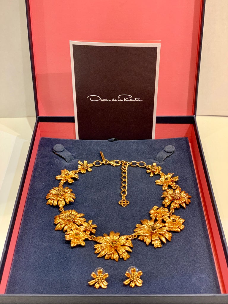 Created by the elite fashion house of Oscar de la Renta, this very substantial statement necklace features a daisy-chain of gleaming blossoms alight with sparkling Swarovski topaz crystals and is accented by matching classic flower button earrings.