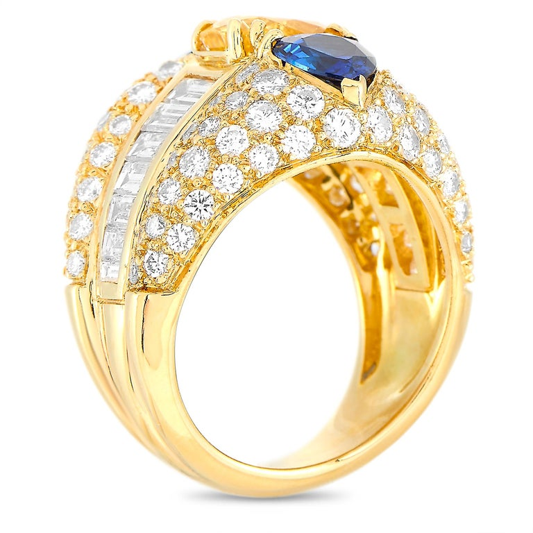 This Oscar Heyman ring is made of 18K yellow gold and weighs 13.8 grams. It boasts band thickness of 6 mm and top height of 6 mm, while top dimensions measure 18 by 20 mm. The ring is set with diamonds and sapphires that total approximately 2.50 and