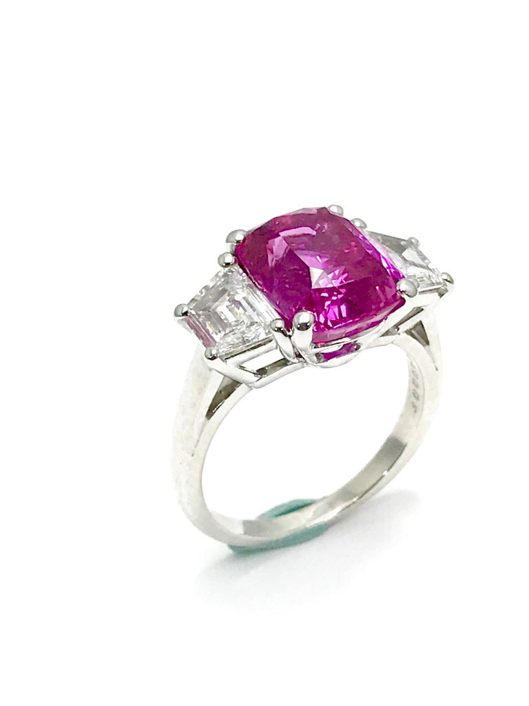 An absolutely stunning Oscar Heyman 6.32 carat Pink Sapphire and trapezoid cut Diamond platinum ring.  The Pink Sapphire displays breathtaking color, set in a four prong basket setting with two trapezoid cut Diamonds on either side.  The Diamonds