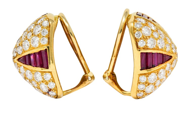 Ear-clips are designed as pyramidal forms  Pavè set throughout by round brilliant cut diamonds weighing in total approximately 4.31 carats; F/G color with VS clarity  Accented by triangular channels of calibrè cut rubies weighing approximately 4.71
