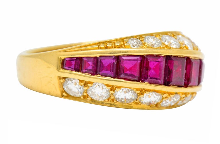 Band ring is designed as three rows of gemstones, slightly torqued  Centering calibrè cut ruby weighing approximately 1.25 carats; slightly purplish-red and very well-matched  Flanked North and South by bead set round brilliant cut diamonds weighing