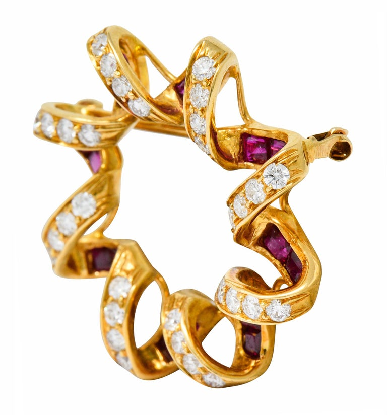 Designed as a stylized starburst with a spiraled gold border  Bead set with round brilliant cut diamonds weighing approximately 0.80 carat; F/G color with SI clarity  With channel set calibrè cut ruby weighing in total approximately 0.95 carat; red