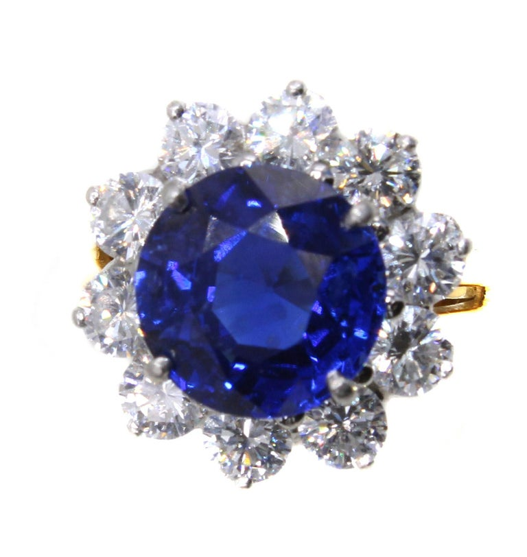 A stunning electric blue Burma sapphire weighing 5.36 carats is the center piece of this diamond platinum and gold ring by Oscar Heyman. The perfectly cut round sapphire exhibits an amazing saturation of color, brilliance and fire. Having the