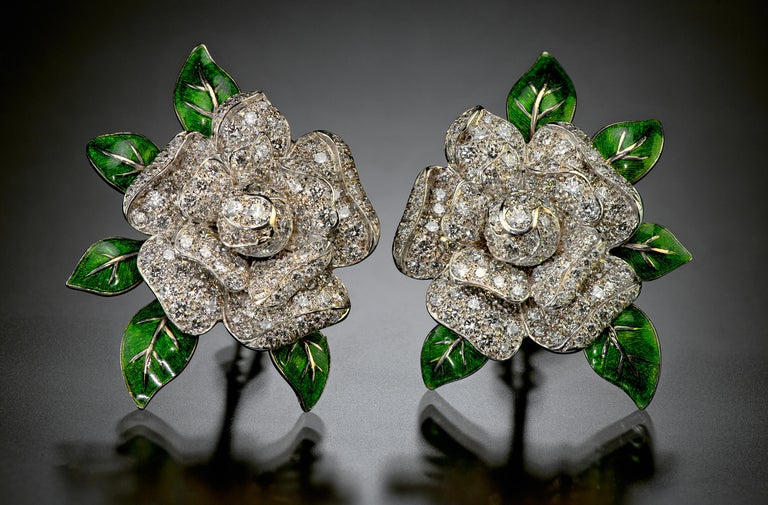 For over one hundred years, Oscar Heyman has been making exquisite jewelry by hand in their New York City studio. In these pleasing gardenia flowering ear clips, 263 round diamonds are set in platinum with green enamel accents. The first Heyman