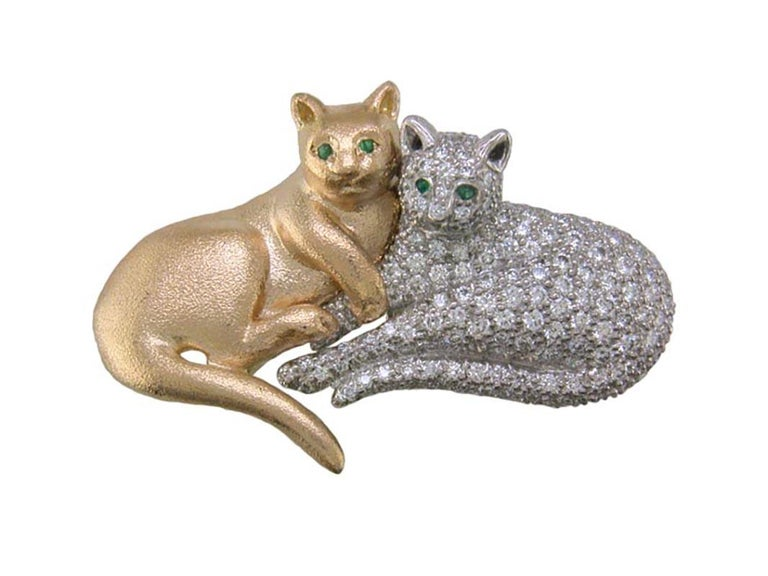 Oscar Heyman 18kt yellow gold and platinum double cat brooch contains a 189 round diamonds weighing 3.14cts (F-G/VS+) and 4 round emeralds as the eyes. It is stamped with the makers mark, 18K PLAT, and serial number 200781.  It measures 48mm in