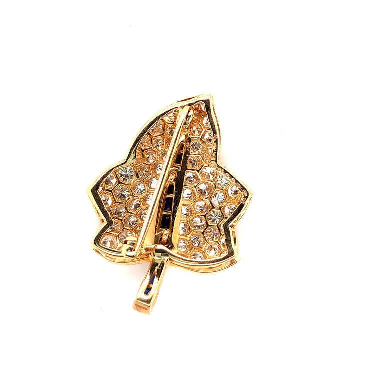 Oscar Heyman 18kt yellow gold maple leaf brooch contains 66 round diamonds weighing 3.22cts (F-G/VS+) and 10 baguette sapphires weighing 0.66cts. It is stamped with the makers mark, 18K, and serial number 200991.  Brooch measures 34mm in length by