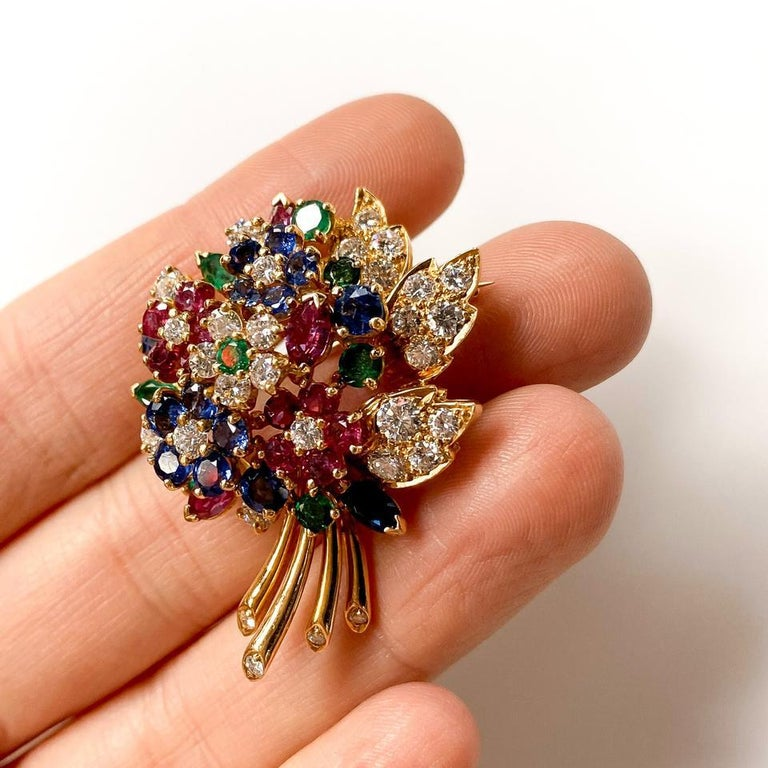 Designed as a bouquet of flowers sapphire, ruby and diamond flowers, with emerald pistils and leaves, set in 18k yellow gold.   With Oscar Heyman 'HB' hallmark.  CONDITION: Pre-owned DESIGNER / HALLMARKS: Oscar Heyman METAL: Yellow Gold GEM STONE:
