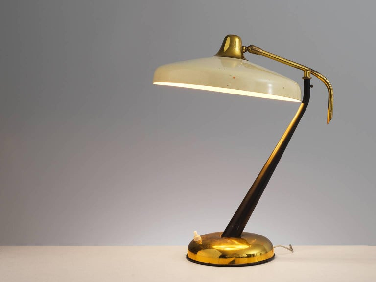 Oscar Torlasco for Lumi, desk lamp in brass, off white metal, Italy, 1950s.  This wonderful curved brass desk light features a brass body and an off white coated shade. The stem of the light features a soft curve. The end of the stem ends in a