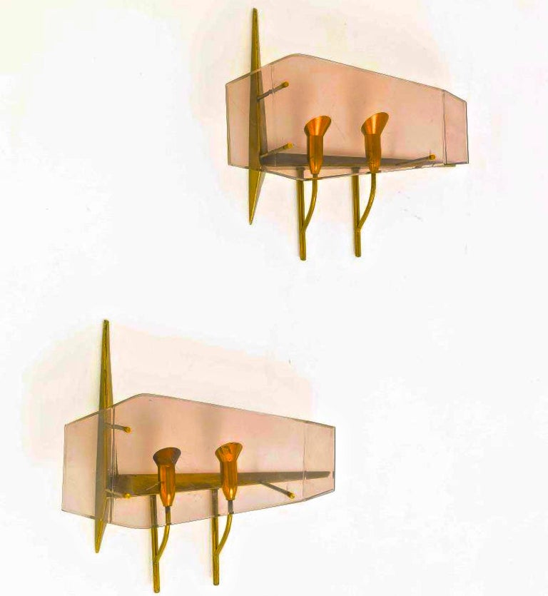 Very rare pair of wall lamps, circa 1960 designed by Oscar Torlasco for Stilux Milano.  Double light brass structure with color tinted perspex.  Each sconces holds two candelabra size bulbs up to 60 watts each. Rewired for US. Note how each socket
