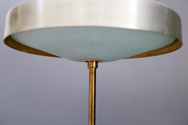 Rare table lamp created by Oscar Torlasco for Lumi in 1950. The lamp was published in Domus, a furniture magazine. Its particularity is its semi-spherical light holder, almost reminiscent of a UFO shape. The structure and base is in brass. Note the
