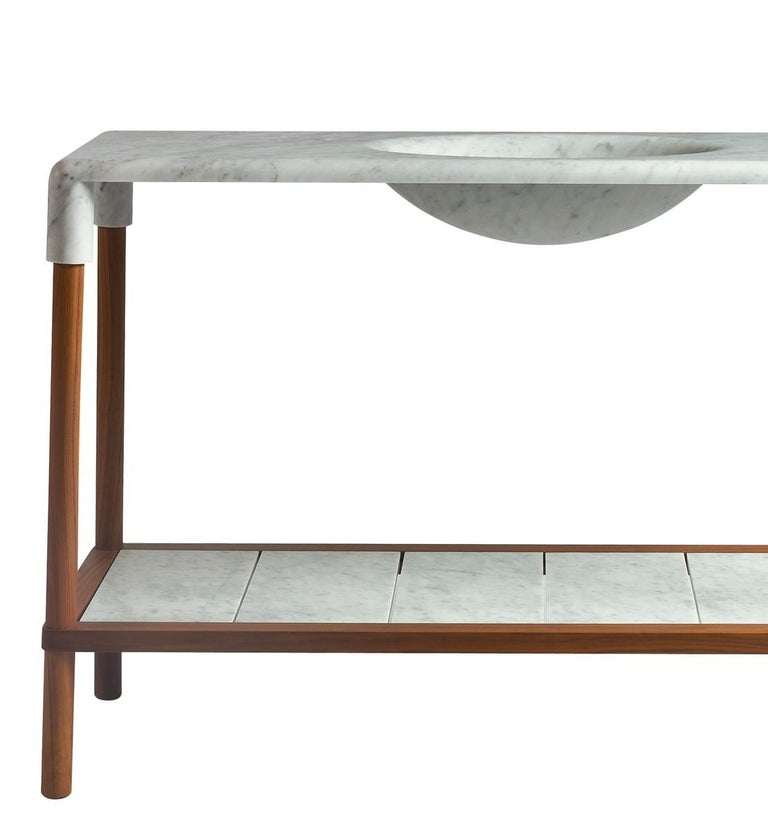 Designed by Gritti Rollo, this elegant console is part of the Oslo collection, an elegant series of pieces of midcentury inspiration that boast a top in marble bending at the corners to enclose the structure in walnut. The standout element of this