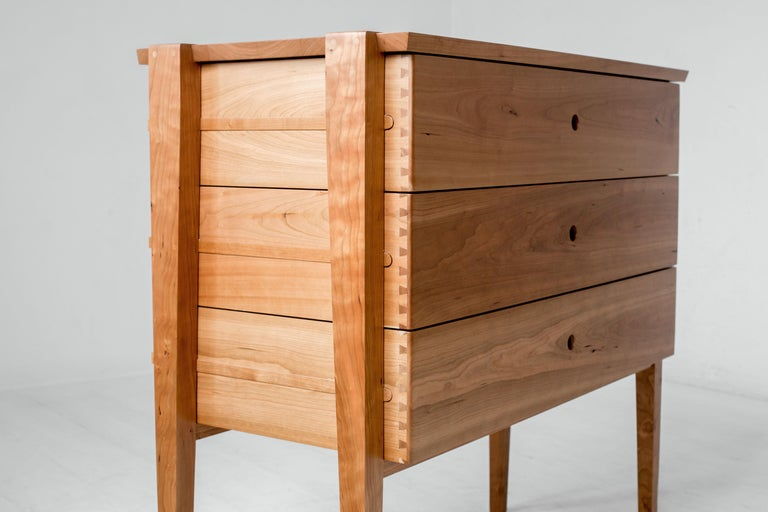 Simplicity and beauty intersect in this modern interpretation of a tradition design. Our Oslo cherry dresser features three deep dovetailed drawers nestled in an open frame. The drawers slide smoothly on waxed wood rails, revealing the mechanism at