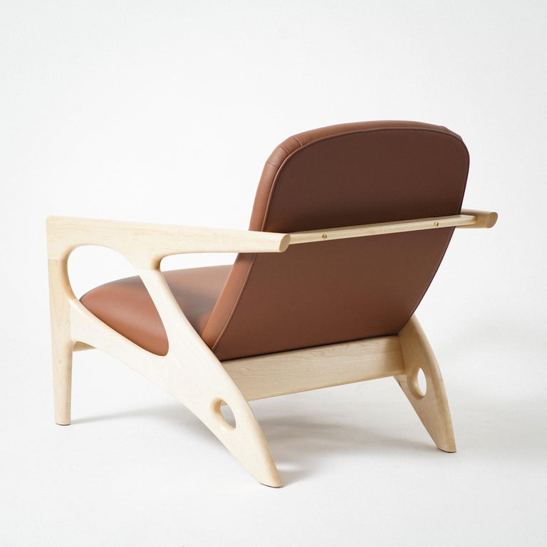 Phloem Studio osprey lounge chair is a modern contemporary lounge chair with a exposed solid maple hardwood frame that cradles an upholstered shell, with leather upholstery. The frames are handcrafted in walnut, maple or black. Leather upholstery is