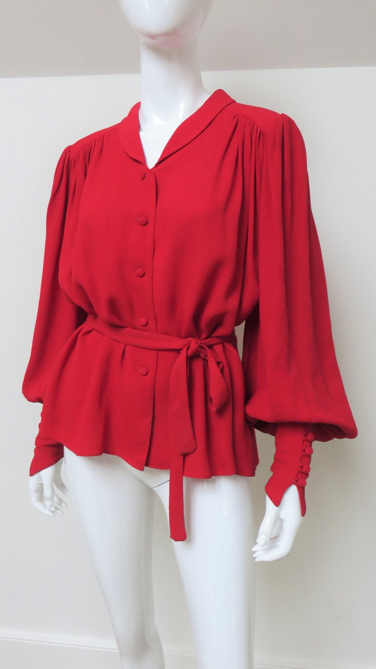 A fabulous red crepe blouse shirt from Quorum designers Ossie Clark and Alice Pollack.  It has a small rounded shirt collar, back yoke and full sleeves with wide pointed self covered buttons and loops cuffs.  The shirt body and sleeves gather from