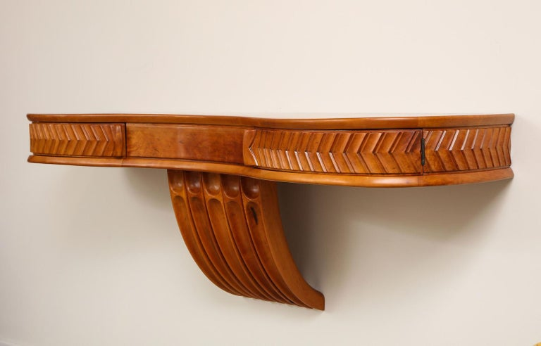 Wall Mounted Console Table by Osvaldo Borsani for ABV.  Console table of maple with carvings, central support & 2 drawers that each open on a concealed pivot.   Wood has recently been refinished.  Authenticated by the Archivio Osvaldo