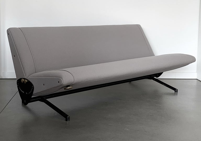 Iconic D70 fully adjustable sofa designed by Osvaldo Borsani for Tecno, circa 1950s. Convertible into a daybed when folded flat. Newly upholstered in a light gray wool fabric by Maharam / Kvadrat with new foam throughout. The base is black enameled