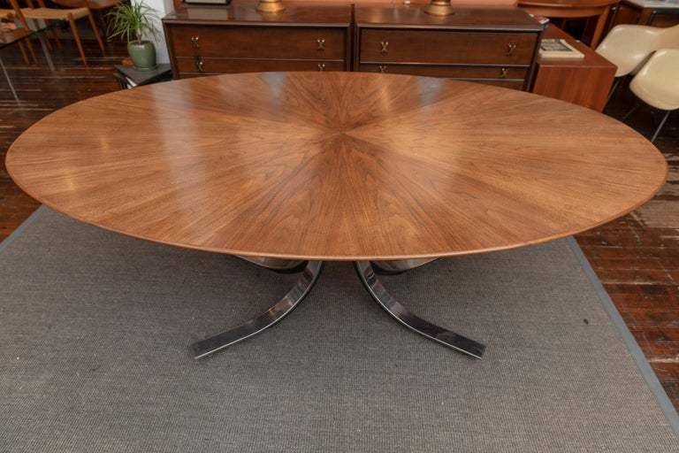 Osvaldo Borsani design walnut oval dining table for Stow Davis. Gorgeous starburst pattern veneered top just newly refinished with a custom made under frame to raise the table to standard dining height.  Steel and chrome splayed leg base with