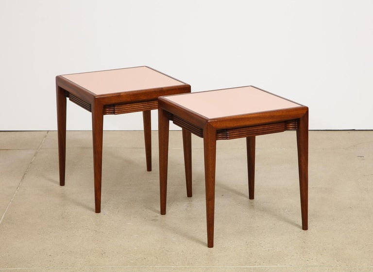 Pair of mirrored-top, low side tables by Osvaldo Borsani. Low square tables of mahogany and inset rose colored mirrored tops with fluted facing on all four sides. One small center drawer per table. A variation of this model lives in the Casa Borsani