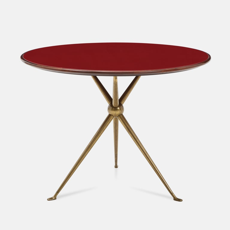 Designed by Osvaldo Borsani and manufactured by Arredamenti Borsani Varedo, Milan in 1940s, very rare matched pair of round side tables with wood top and inset reverse painted deep red glass atop gilt brass tripod base. Beautifully modern lines and