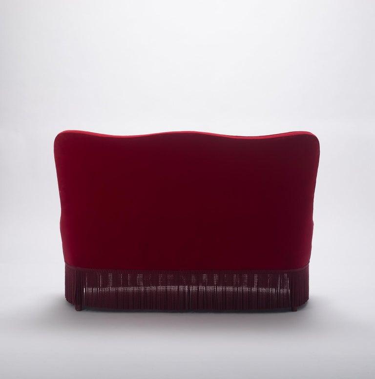An Italian Osvaldo Borsani crimson red velvet banquette with red bouillon trim.