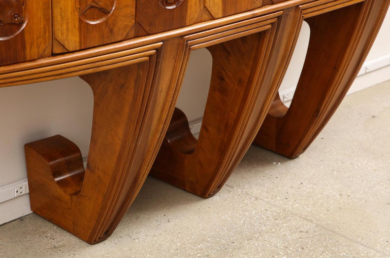 Wall-mounted sideboard by Osvaldo Borsani for ABV. 2-door wall-mounted sideboard of Italian walnut with fauna-motif carvings. Interior of red mahogany. One door opens to reveal storage with 1 shelf. The opposite side opens to reveal 5 shallow