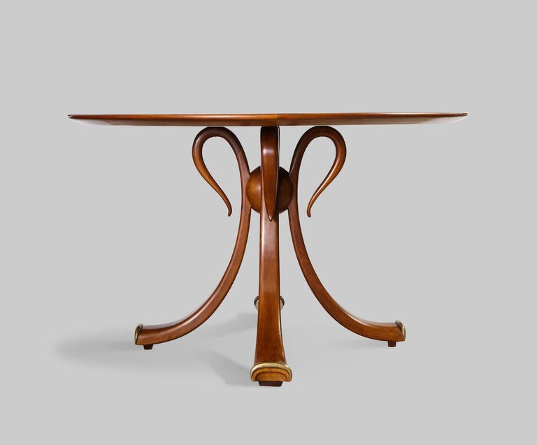Rare center/ games table, by Osvaldo Borsani. Walnut pedestal table of 4 curved wood fronds with brass trim at feet. Solid center wood ball and radius veneered circular top. Produced by Arredamenti Borsani Varedo with label to underside of top.