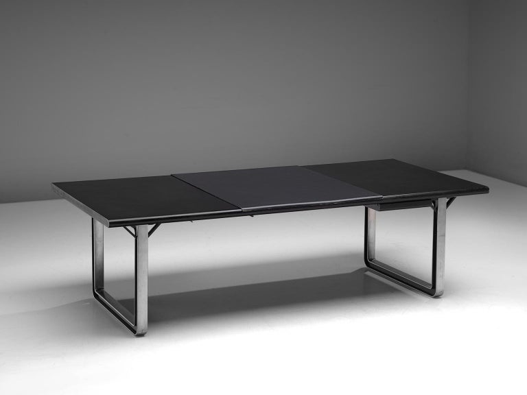 Osvaldo Borsani for Tecno, desk/writing table, aluminum, lacquered wood and leather, Italy, 1970s.  Desk table with a black top. The base consists of a two metal frames. The base creates an open character with the dark top. It was at the time that