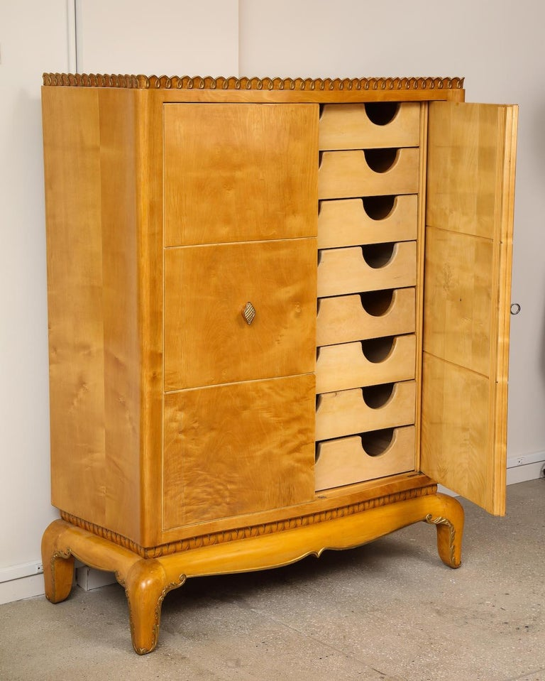 Wardrobe Unit by Osvaldo Borsani for ABV. Maple, burled maple, painted wood. Cabinet with stylized feet, carvings and gold-painted accents. Doors open to reveal 8 interior drawers. Exterior wood has been recently refinished. Provenance: Borsani