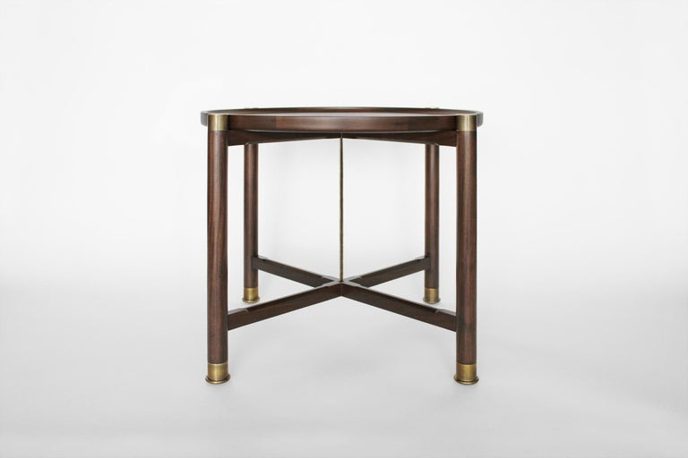 The Otto side table is a generously proportioned table with a simple, well, articulated form. Available in walnut or oak, it features a round coupe top, substantial antique brass fittings, a central brass stem, and sleek chamfered stretchers. The