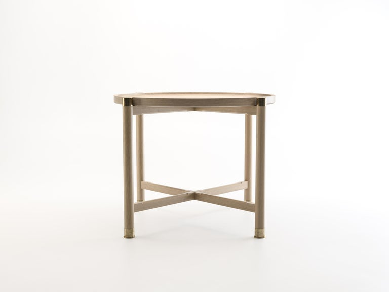 The Otto side table is a generously proportioned table with a simple, well-articulated form. Available in oak or walnut, it features a round coupe top, substantial antique brass fittings, and sleek chamfered stretchers. The epitome of understated