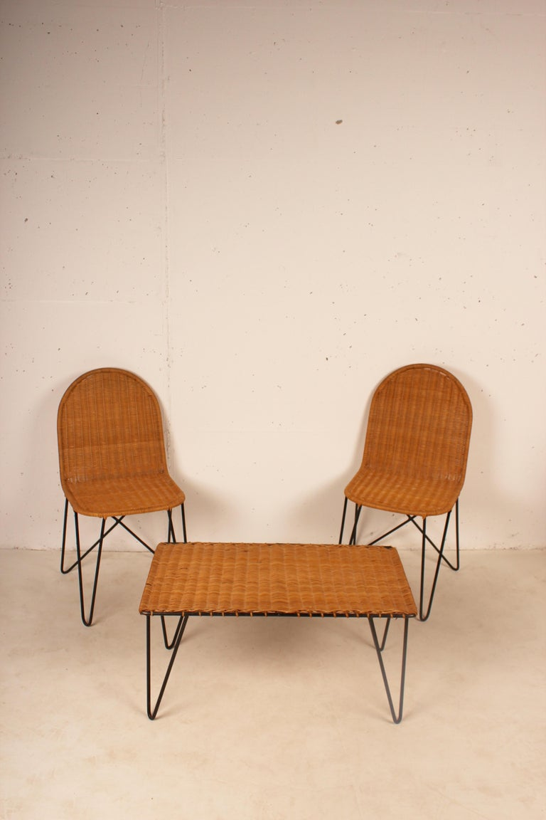 Outdoor wicker set, coffee table and 2 chairs by Raoul Guys, France 1950, wicker on lacquered metal base.  Measures: coffee table 73 D x 42 W x 37 H cm chair 52 D x 38 W x 77 H cm.