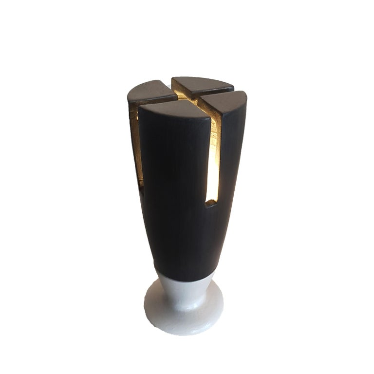 Table lamp made of bucchero and earthenware, which recalls medieval European architecture. This item brings together minimalism and postmodernism. The light radiating through the slits give this object a magical and timeless effect. It is a