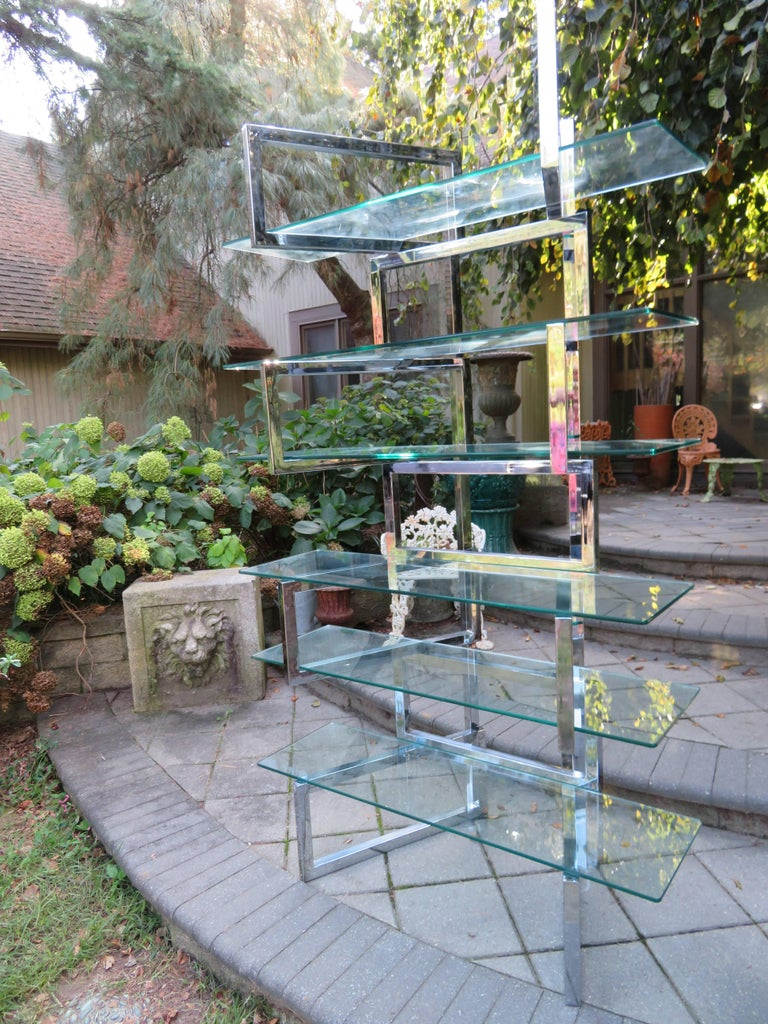 Over the top Milo Baughman chrome and glass étagère. The chrome-plated steel heavy square tubes are hinged to allow for the units panels to pivot. The chrome is very nice with only minor signs of wear. The glass shelves can be arranged in different