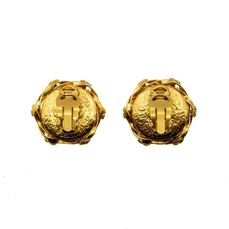 Outstanding 1995 Faux Pearl and Gilt Metal Clip-on Earrings. These earrings feature a large central faux pearl with 6 House logos woven around the edge with gold coloured gilt metal. This piece features the Chanel authenticity plaque. Provenience