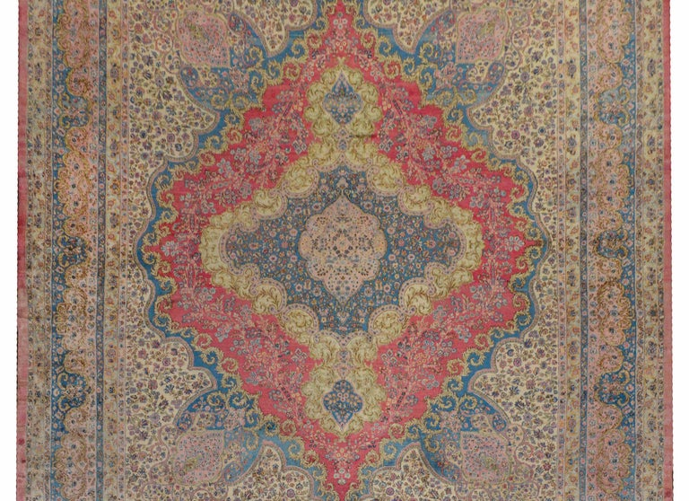 An outstanding early 20th century palatial Persian Kirman rug with an incredible large-scale floral diamond medallion woven in light indigo, gold, pale green, and pink amidst a field of flowers on a cream colored background. The border is Grande