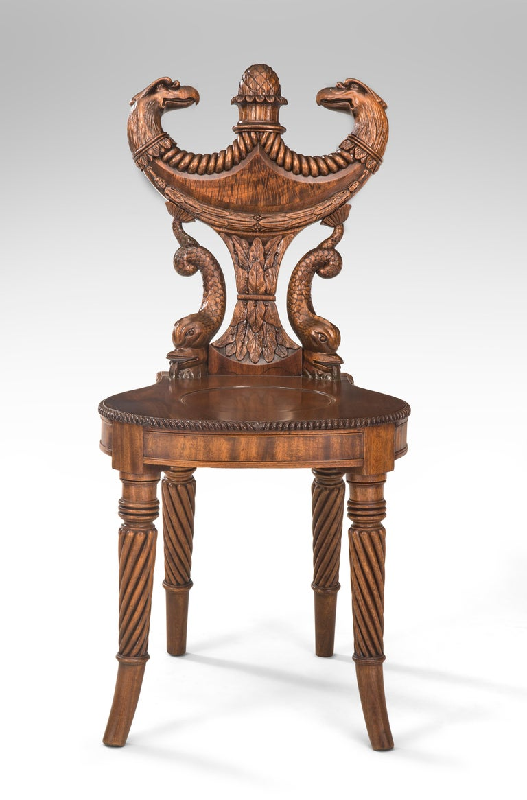 Outstanding English Regency mahogany hall chair Late 18th or early 19th century A highly original hall chair of ingenious design and superb carving, a rare and exceptional chair. The double headed eagle shield back supported by flanking dolphins,